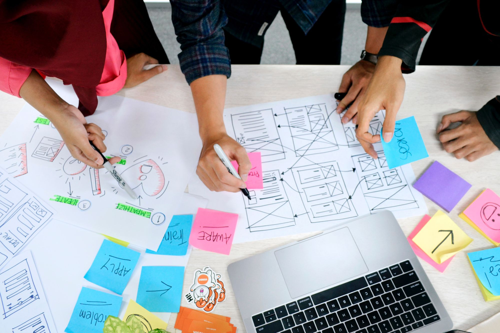 Three people building out a highly functional wireframe with multi-colored sticky notes and illustrations.