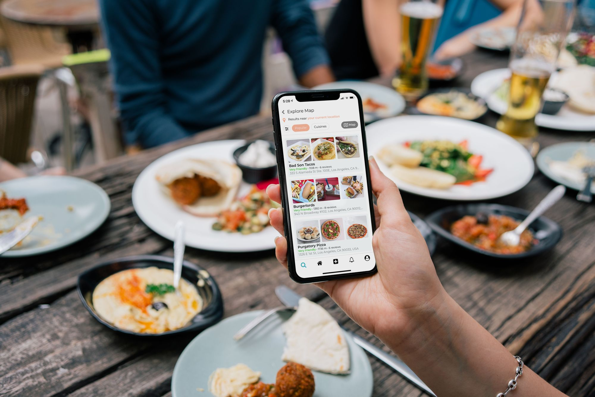 A woman at a table full of Mediterranean food using one hand to maneuver through an app on her smartphone.