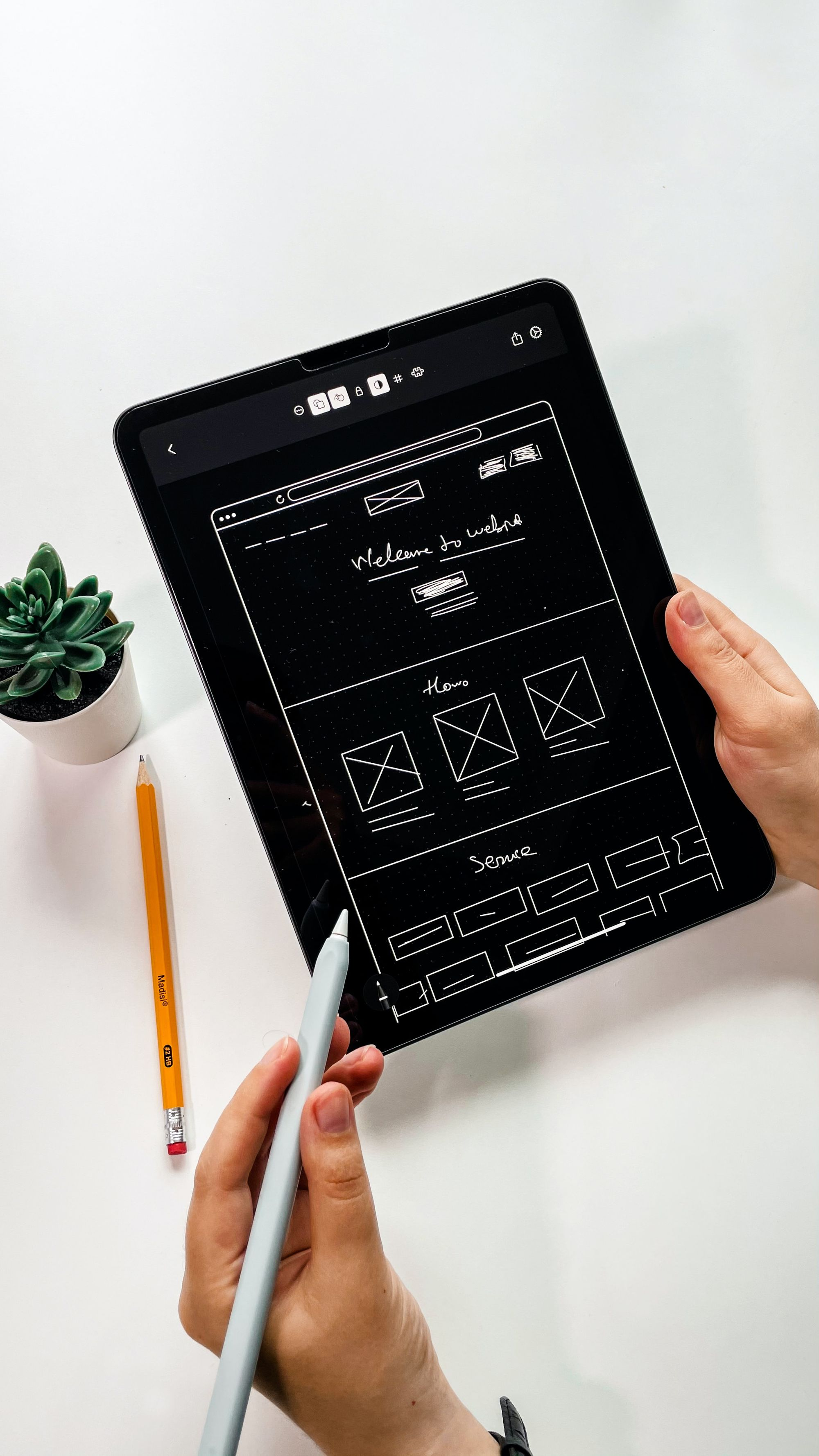 A person sketching out a website wireframe on a tablet with a gray stylus.