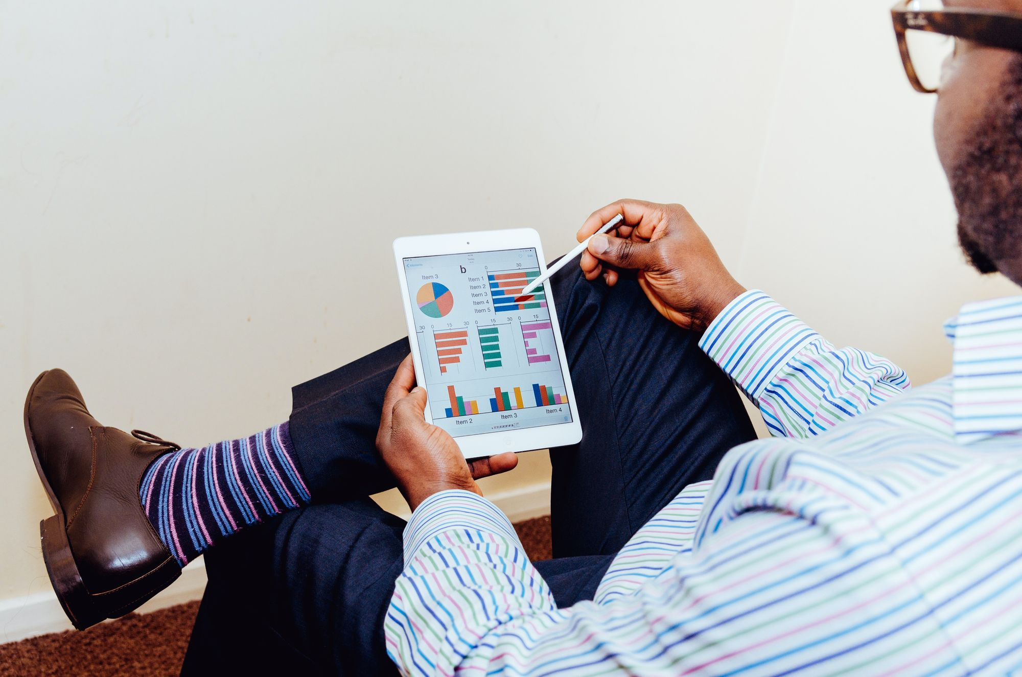 A man in striped socks, loafers, slacks, and a button down shirt reviewing analytical data on a tablet.