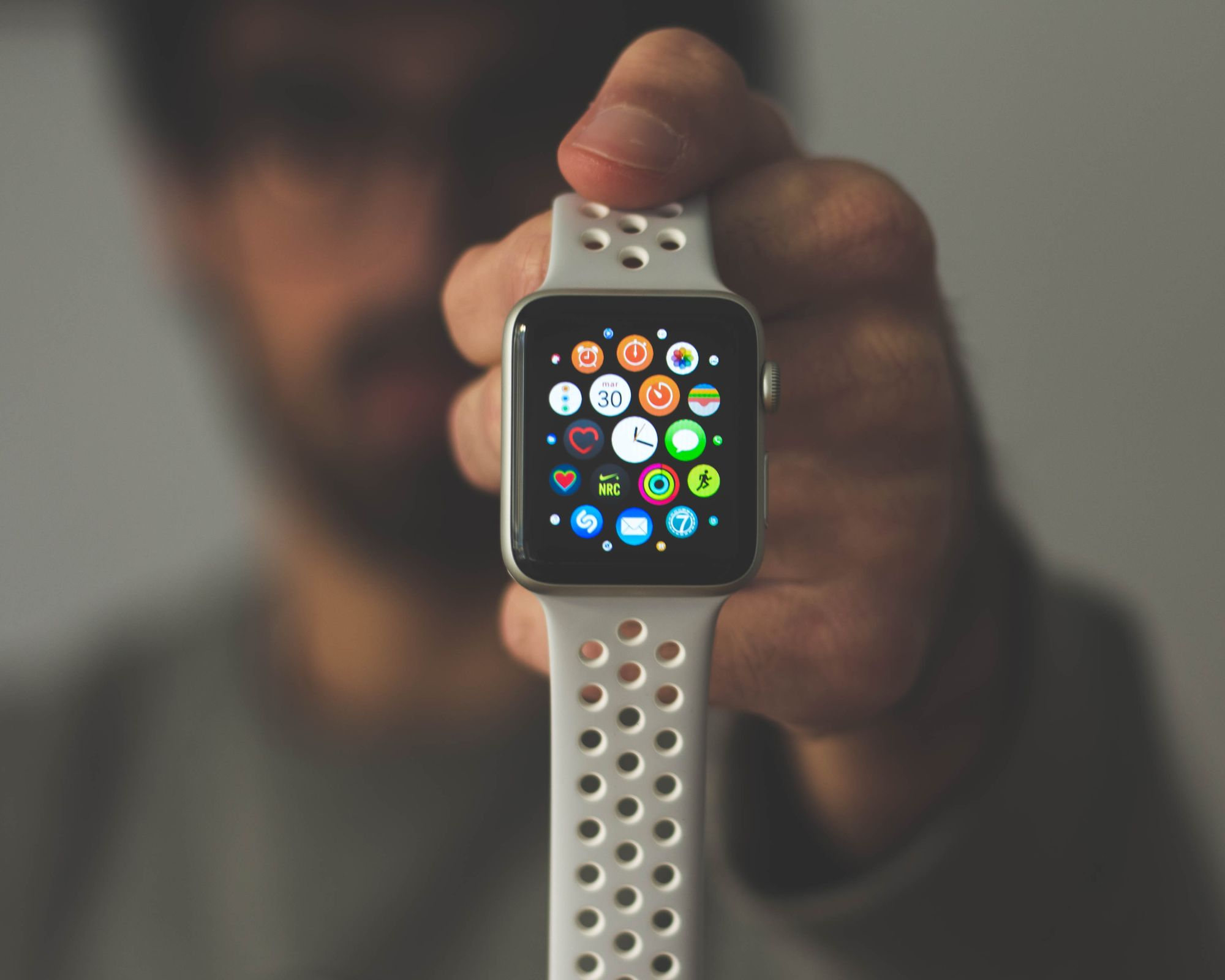 A man holding a smart watch full of different apps in front of him.