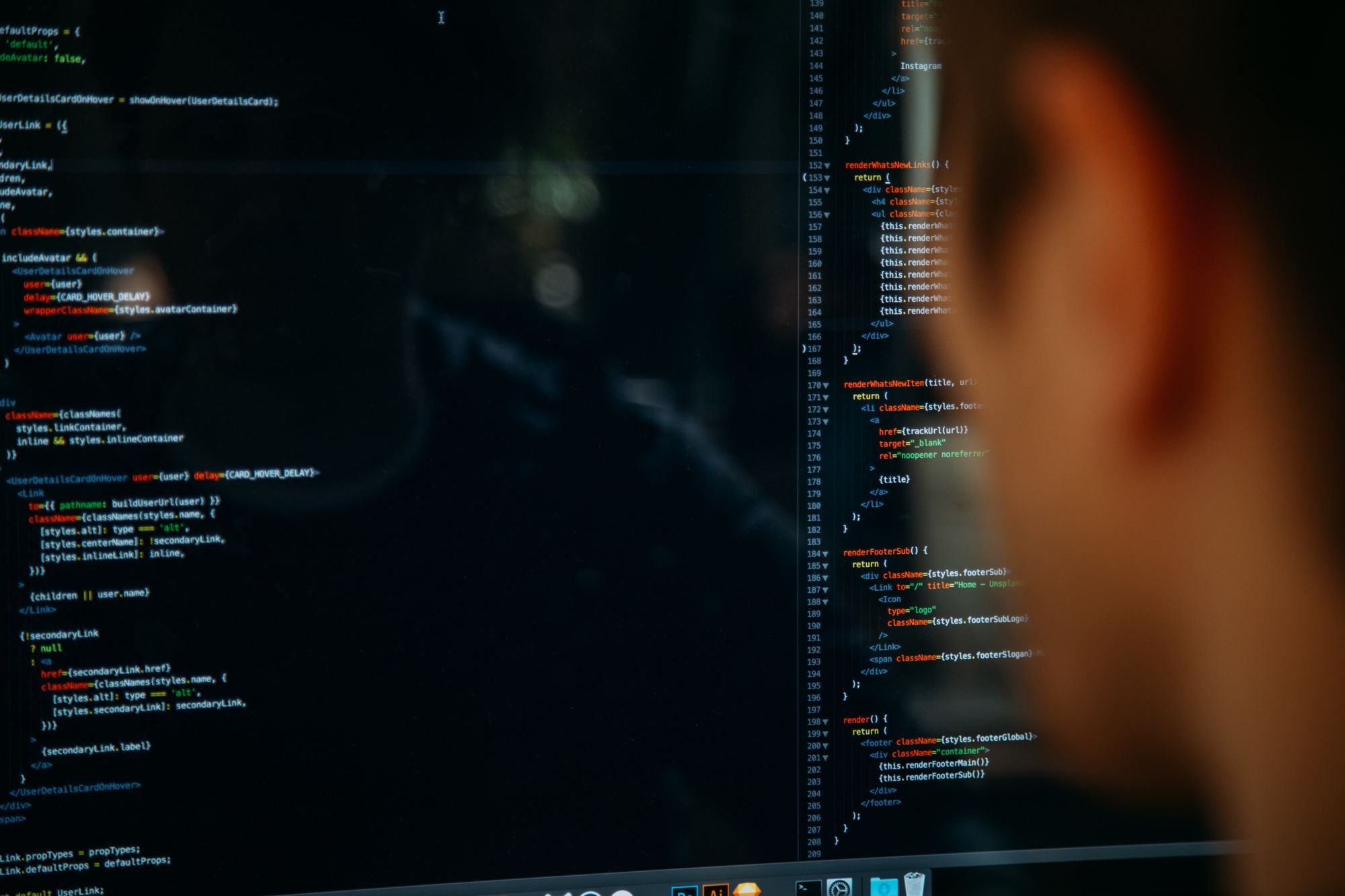 A person reviewing code on a large, dark monitor.
