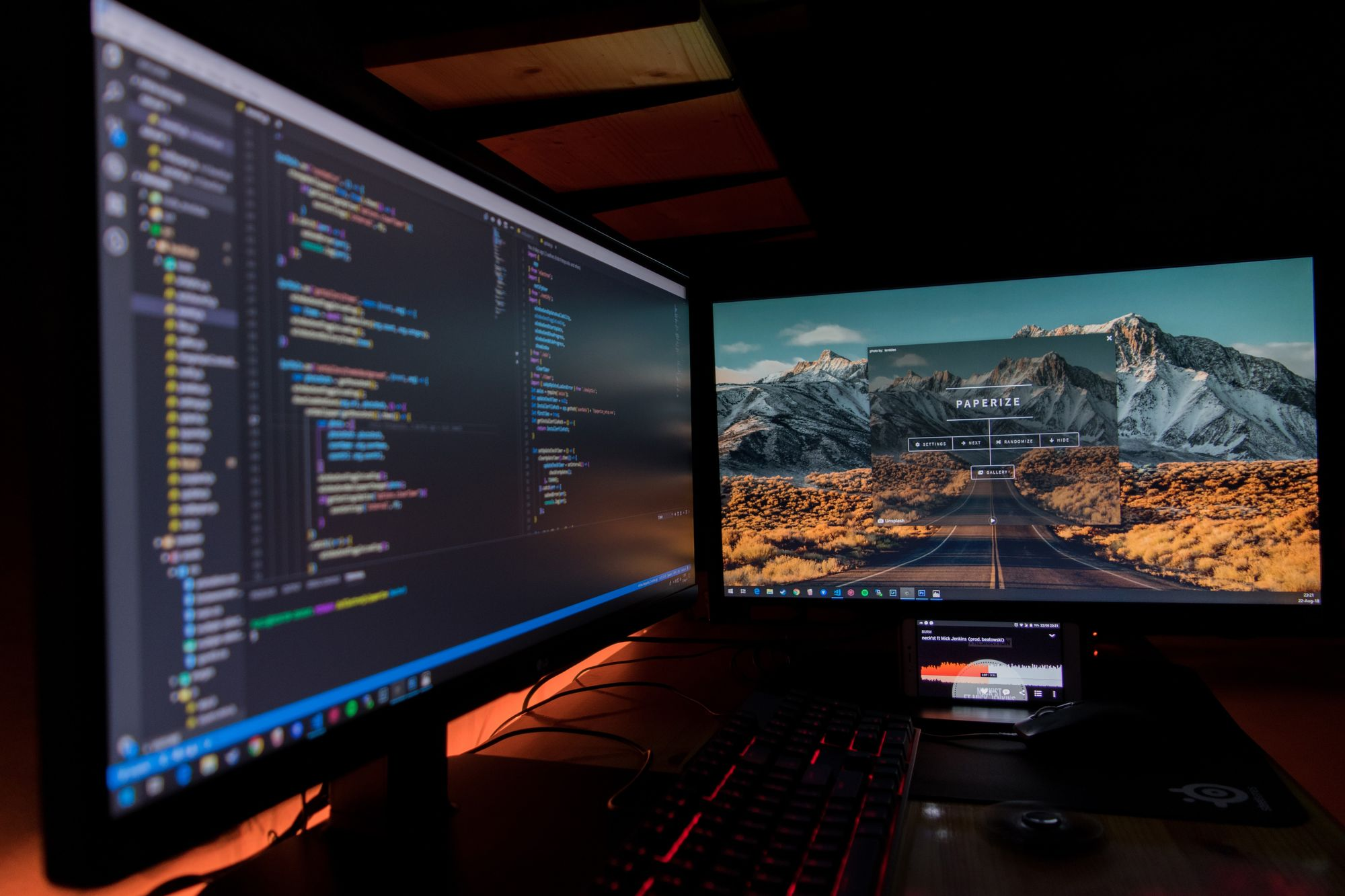 A dual monitor setup with code on the left and a mountainous background with a road leading off into the distance on the right.