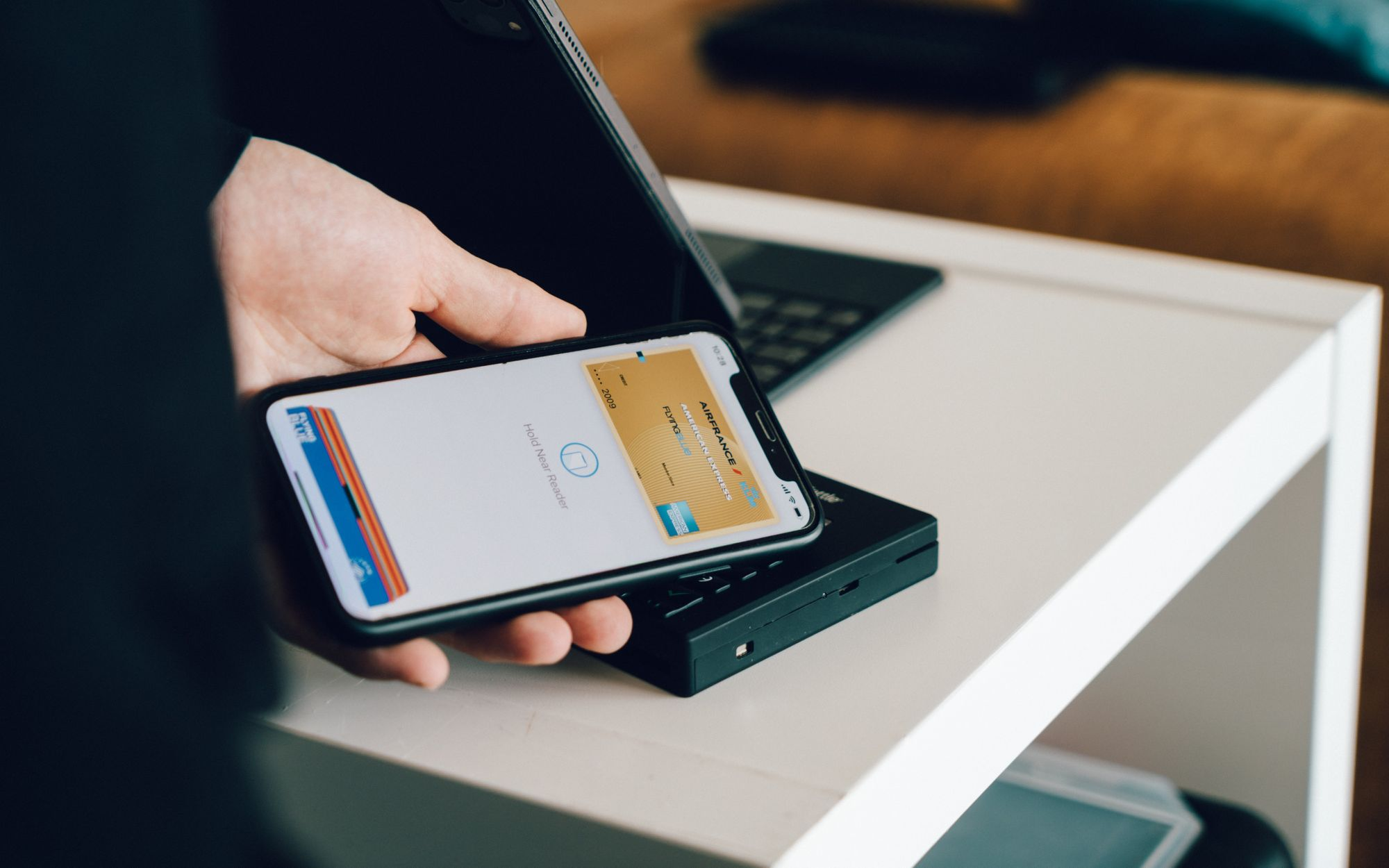 A person using the Apple Pay mobile Wallet to purchase something at a shop.